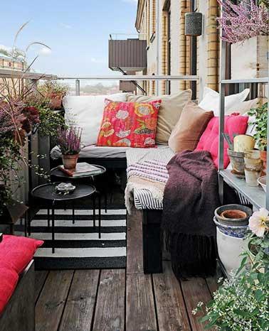 Un angle de balcon aménagé en coin cosy à l'aide d'une banquette recouverte de gros coussins colorés rose et beige. Parquet vieilli et table basse gigogne ajoutent convivialité à la terrasse