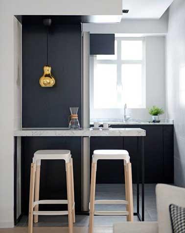 Petit coin repas avec plateau en marbre posé sur deux pieds en fer noir. Complété par des chaises bar en bois et plastique blanc et une suspension dorée, il fait la déco design de la cuisine