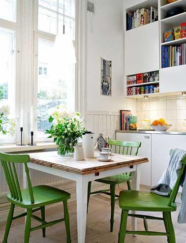 Table avec plateau bois pliable pour faire un coin repas gain de place. Assortie avec trois chaises en bois vertes pour colorer meuble de cuisine et murs blancs.