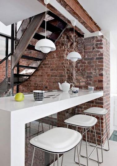 Un mur de brique sous un escalier se transforme en petit espace repas. Une solution gain de place adaptée ici autour d'un mobilier de cuisine blanc pour sublimer l'aspect brut du mur.
