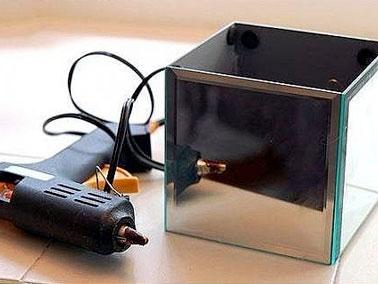 Cinq miroirs sont collés entre eux à l'aide d'un pistolet à colle ou d'une colle prise rapide pour former un carré. L'ensemble est maintenu quelque instant à l'aide d'un élastique