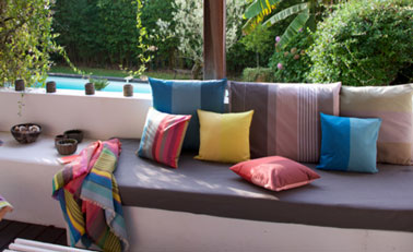 Plaid Surfing et mlx de coussins coloris Zanzibar, Luz Atlantique, Luz Limonade, Luz Garance, Luz céladon et Rhune donnent leurs couleurs à une terrasse de jardin ensoleillée. Tissage de Luz