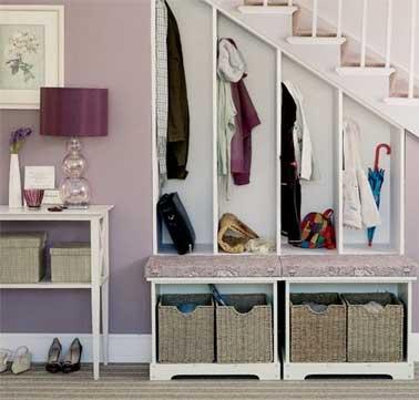 Mini dressing aménagé dessous l'escalier d'une entrée. Aménagé avec quatre placard ouverts et deux blocs de rangement fait avec des paniers en osier et recouverts de coussins couleur mauve
