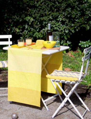 Sur la table de jardin en fer blanc, chemin de table jaune à larges rayures collection Luz Limonade. Galettes de chaise modèle Amaya. Collection Tissage de Luz