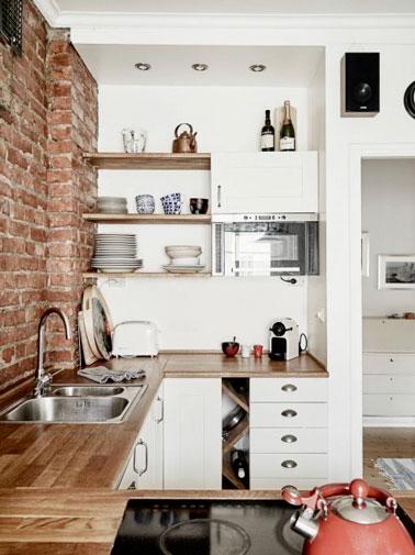 Meubles de cuisine et peinture blanche valorisent une crédence de cuisine réalisée en mur de brique. Les détails poignets des tiroirs et des étagères en bois ajoutent de la personnalité à la pièce