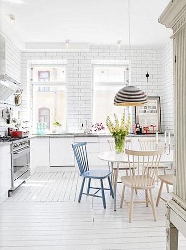 Carrelage métro sur les murs, parquet blanc sur le sol, la cuisine joue les gammes de blanc dans toute la pièce. Plan de travail en marbre et déco rétro apportent les notes de couleurs