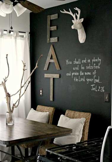 Peinture tableau noir personnalisée avec lettres en bois et tête de cerf en plâtre sur un mur de la salle à manger. Déco valorisée avec coussins, luminaires et rideaux blancs.