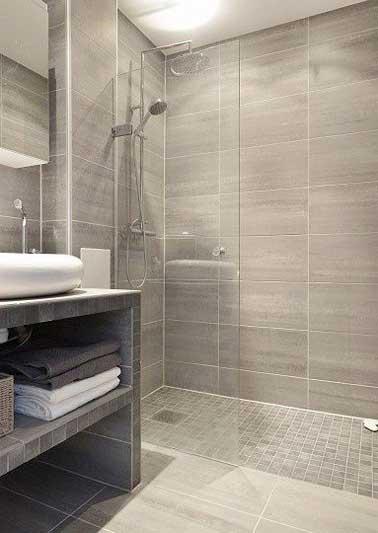 Une douche à l'italienne en carrelage imitation bois et petits carreaux de grès sur le sol. Assortie avec un plan vasque carrelé composé de niches de rangement
