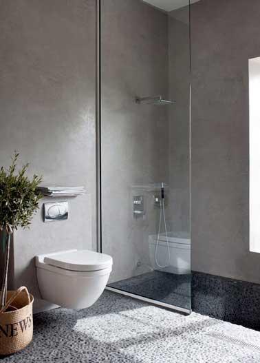 Douche à l'italienne dans une petite salle de bain avec sol en carrelage galet et murs en béton ciré. Une association de matériaux chic et tendance pour faire la déco désign