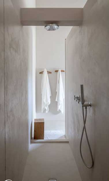 Une douche à l'italienne construite dans un espace étroit en béton ciré. Simple et minimaliste, elle possède une douche pluie encastrée dans un coffrage sur mesure.