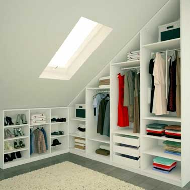 Réaliser un dressing sur mesure c'est une solution pour gagner de la place. Ici quatre armoires avec penderie et tiroirs suivent la pente du toit. Range chaussure et étagères basses complémentaires.