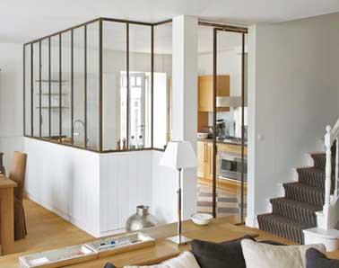 Cuisine atelier séparée du salon avec verrière et soubassement en bois blanc. Les meubles de cuisine en bois créent une continuité avec le parquet et les meubles du séjour.