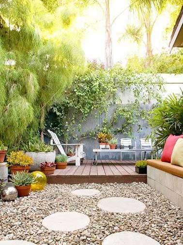 Terrasse aménagée en deux parties. Coin détente pour la terrasse surélevée en teck agrémentée de chaises longues et espace jardin zen avec des pas japonais sur un parterre de galet.