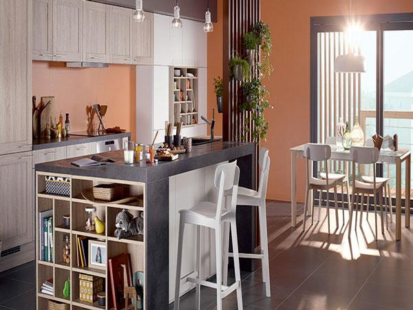 Cuisine américaine familiale aménagée avec un plan de travail anthracite prolongé d'une niche de rangement et des façades de meubles finition chêne clair et blanc mat.