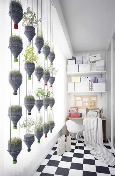 Mur végétal fabriqué avec des bouteilles en plastiques coupées et placées dans une structure métal. Fleuri de blé et de lentilles il anime la pièce et lui donne des couleurs