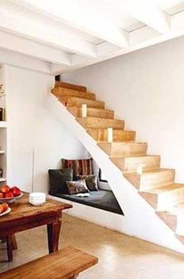 Coin détente cosy installé sous l'escalier en bois. Aménagé avec un matelas de sol et des gros coussins chocolat contre le mur blanc, il s'intègrent parfaitement à la déco de cette pièce.