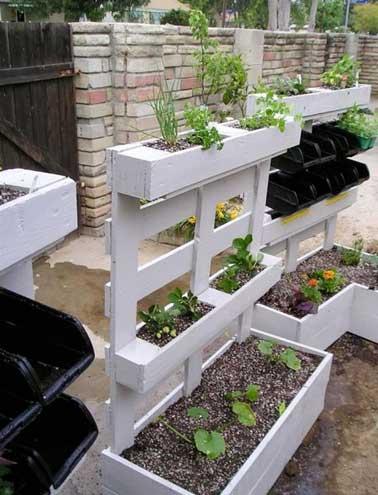 Jardin potager suspendu fait avec des palettes bois peintes en gris. Assemblées entre-elles pour former trois caissons de tailles différentes elles font la déco d'extérieur.