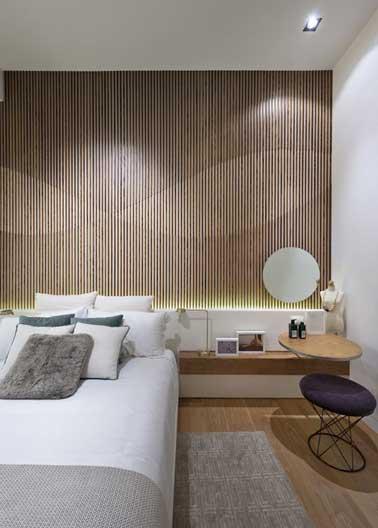 Tête de lit déco graphique dans la chambre avec un panneau décoratif. Table de chevet et tabouret design assortis à la console tête de lit reprennent en écho les formes géométriques du panneau