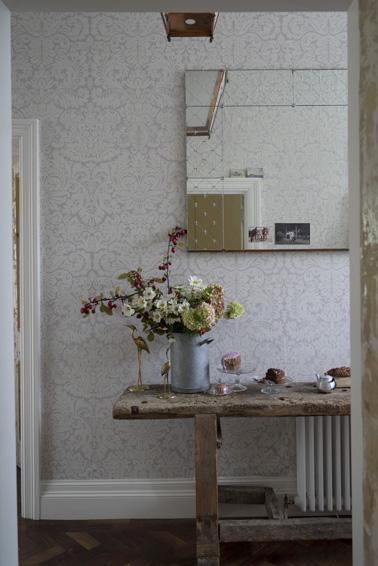 Inspiration du 19ème siècle dans l'entrée avec ce joli motif de papier peint et sa couleur douce. Une déco qui habille élégamment la pièce judicieusement soulignée par de belles fleurs posées sur la table en bois.