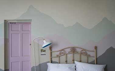 Des nuances de peinture sont utilisées en camaïeux pour peindre un décor dans la chambre. Dessiné sur le mur contre le lit, ce décor fait aussi une tête de lit originale