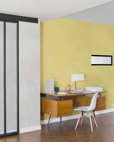 Coin bureau éclairé par la peinture à effet nacré jaune. Composé avec bureau en bois, chaise coque blanche à pieds bois, et lampe de bureau blanche, il donne un ton scandinave à l'entrée