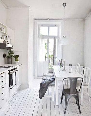 Un parquet blanc dans une petite cuisine monochrome animée avec des détails acier, une chaise vintage, une hotte en inox, des coussins de chaises gris et une suspension en verre mat.