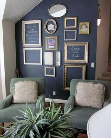 Des cadres vides suspendus contre un mur peint avec une peinture tableau noir font la déco du salon. De toutes les tailles et les formes ils créent une déco cabinet de curiosité