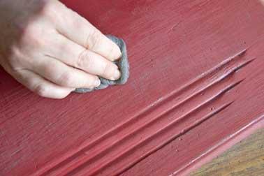 Polissez le meuble de cuisine avec une laine d'acier en effectuant des petits cercles. Cette étape permet d'atténuer les rayures faites par la papier de verre et d'obtenir un aspect satiné