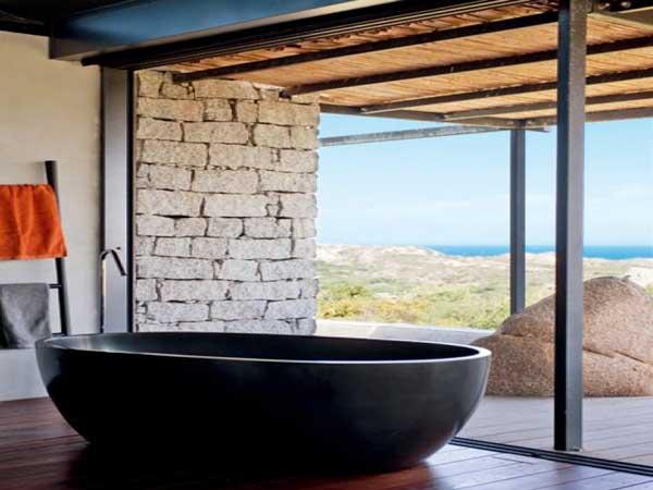 Une salle de bain zen installée derrière une baie vitrée avec vue panoramique sur la mer. Baignoire îlot en résine noire et parquet en bois exotiques sont les atouts majeur de cette déco
