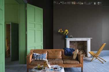 Une peinture de salon cosy avec une peinture murale chocolat. Mariée ici avec une porte peinte dans un ton vert clair lumineux un canapé en cuir camel et des coussins colorés