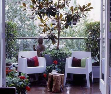Donnez une allure de jardin zen au balcon en adoptant une statue bouddha et deux chaises de jardin aux lignes incurvées. Magnolia et table de jardin rodin de bois en symétrie quasi parfaite