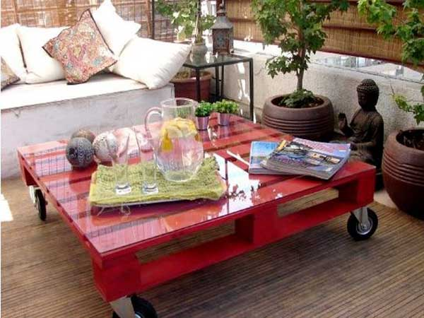 Une table basse palette pour l'extérieur faite avec une couche de peinture rouge et un carré de miroir coupé sur mesure