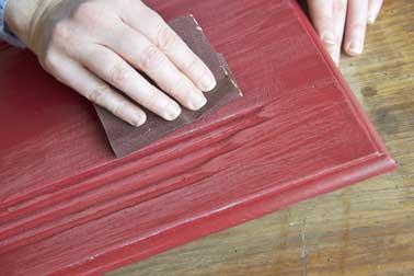 Pour créer l'effet de patine, usez la peinture préalablement appliquée sur le meuble de cuisine en frottant doucement à l'aide d'un papier de verre grain moyen.