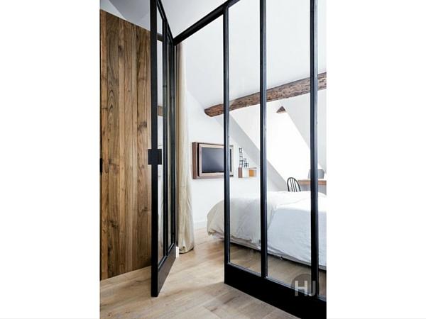 Une verrière industrielle compartimente l'intérieur et définit l'espace sans alourdir dans cette chambre en sous-pente. On aime le contraste entre les montants métalliques et les poutres naturelles.