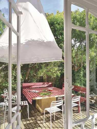 Nichée au milieu de la végétation cette terrasse accueille toute la famille autour de sa grande table en bois. Voile d'ombrage et sol en bois souligne sa convivialité