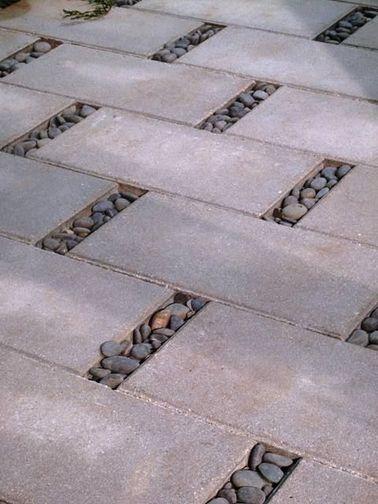 Les dalles de béton sont un moyen facile d'aménager votre allée de jardin, comme ici où elles sont disposées en décalé. Pour combler les trous, on a utilisé de simples galets.
