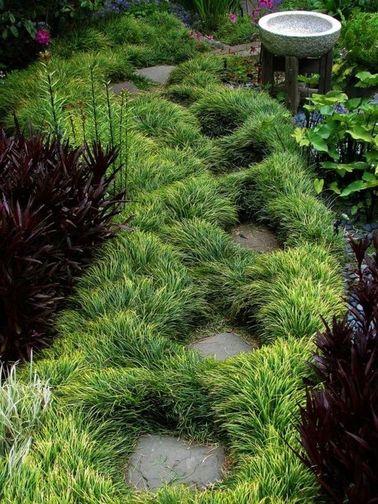 Une allée de jardin japonais bordée de touffes de verdure