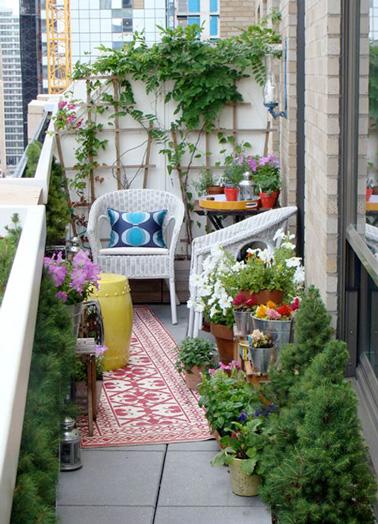 Des chaises en rotin blanc, un joli tapis coloré, des plantes et des fleurs, voilà un aménagement hyper déco sur ce balcon en longueur ! Un espace extérieur idéal pour se relaxer