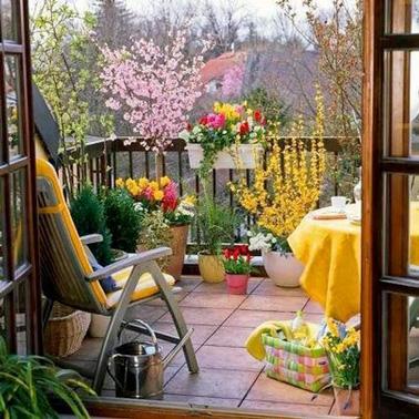 Voilà une jolie déco extérieure aménagée pour votre balcon. Une petite table, un fauteuil confortable, des fleurs pour la couleur et des touches de jaune pour la bonne humeur !