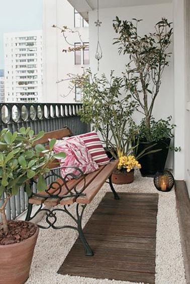 Voici un petit coin lecture aménagé sur ce balcon tout en longueur. Des graviers et une planche de bois pour le sol permettent de créer une ambiance unique, on se croirait dans un petit jardin au coeur de la ville