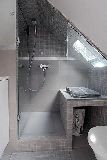Une salle de bain grise et moderne en sous pente équipée d'unbac de douche surélevé sous la plus grande hauteur sous plafond. Dans la douche, le banc sur mesure est recouvert de faïence grise.