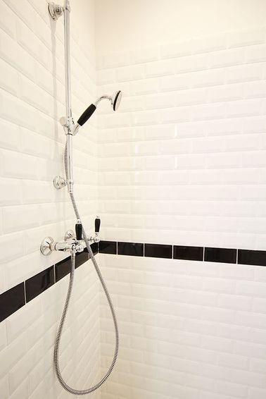 La douche se fait chic et sobre avec un carrelage métro coupé d'une frise noire à hauteur de la robinetterie