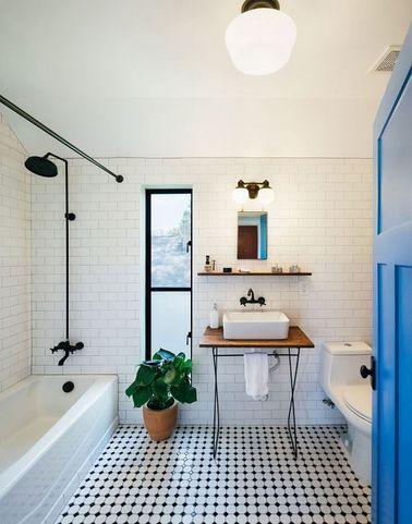 Cette salle de bain vintage exploite de subtils contrastes de blanc et de noir avec le carrelage métro posé sur tous les murs et le carrelage bouchon au sol