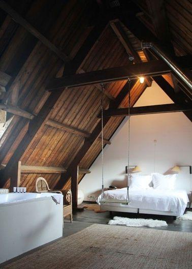 Une chambre avec poutres sous un toit en bois pentu