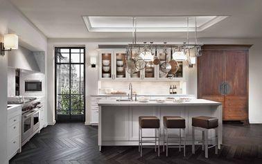 Cette cuisine blanche traditionnelle prend des accents contemporains grâce à un éclairage soigneusement étudié qui donne du volume à la pièce et compense le manque de lumière.