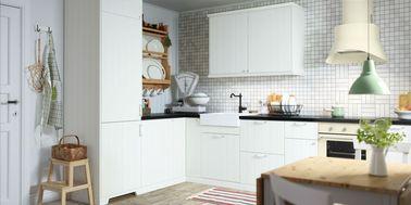 Une cuisine blanche se prête à tous les styles, comme ici avec un look campagne chic chaleureux rendu par des poignées style ancien, des façades rainurées et une crédence en petits carreaux.