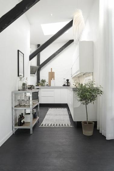 Une cuisine ouverte permet d'abattre les cloisons pour faire faire entrer plus de lumière dans un appartement sous les toits. Le blanc très lumineux contraste avec les poutres et le sol noirs.