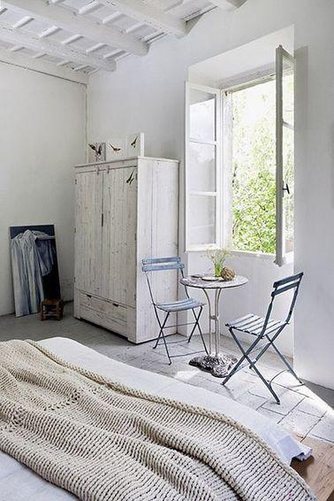 Une déco naturelle dans cette chambre de maison d'été, grâce à une peinture blanche sur les murs et l'armoire ancienne, et un plaid tricoté dans une grosse laine beige.