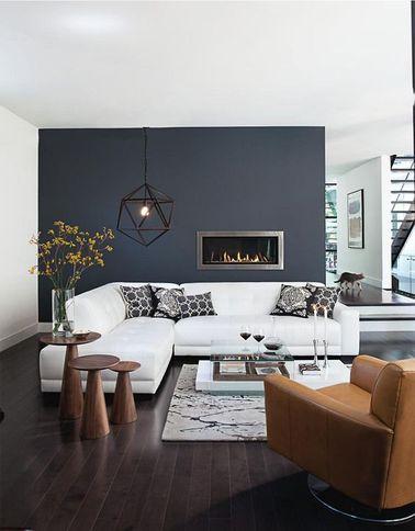 Avec la déco stylée de ce salon gris on ressent un bien-être immédiat. Une ambiance contemporaine et zen à la fois autour d'un canapé d'angle blanc adossé à une cloison gris anthracite séparant de la salle à manger.