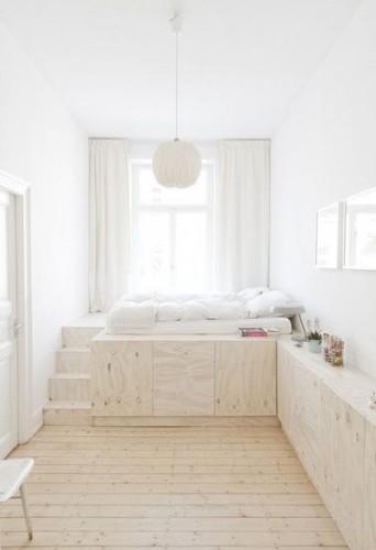 un lit avec rangement dans une chambre blanche. Black Bedroom Furniture Sets. Home Design Ideas